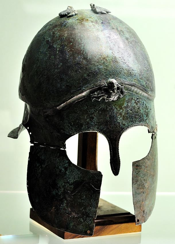 Bronze helmet ornamented with a triton killing a warrior. Attic type. Etruscan work. Mid-5th century BCE. Florence, National Archaeological Museum