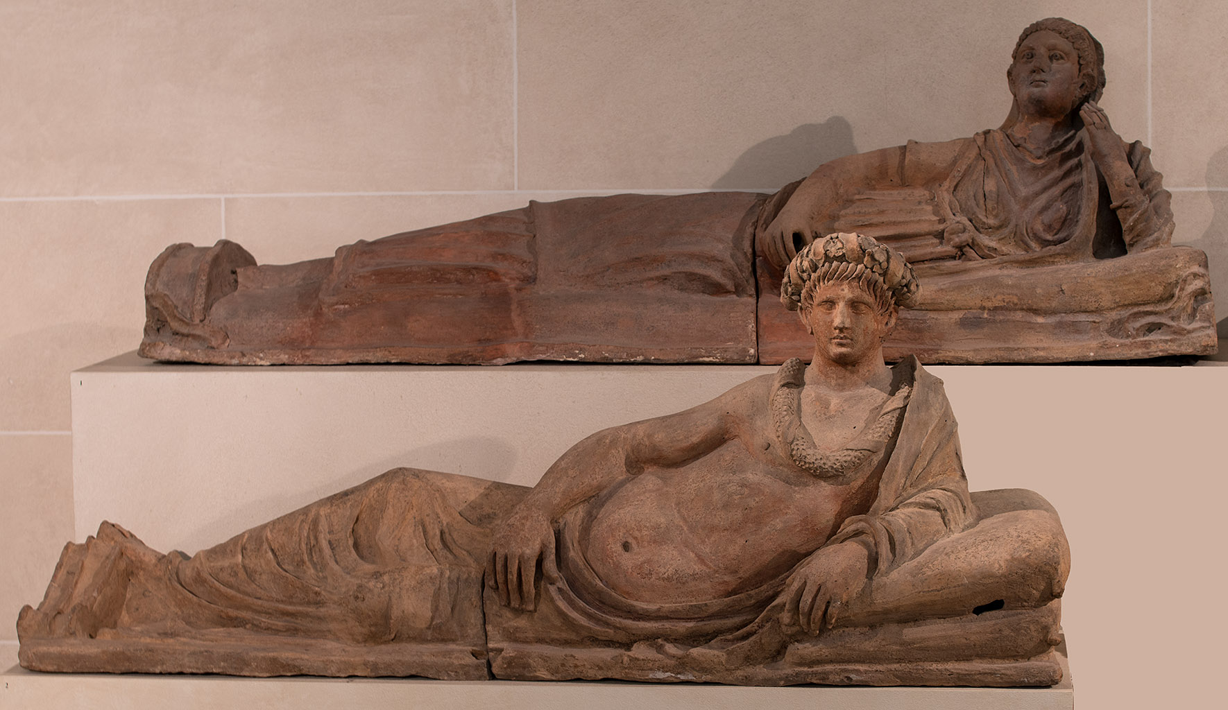 Lid of a terracotta sarcophagus with a figure of a reclining deceased woman. Lid of a terracotta sarcophagus with a figure of a reclining deceased man. Toscana. Terracotta. Mid-3rd century BCE. Paris, Louvre Museum