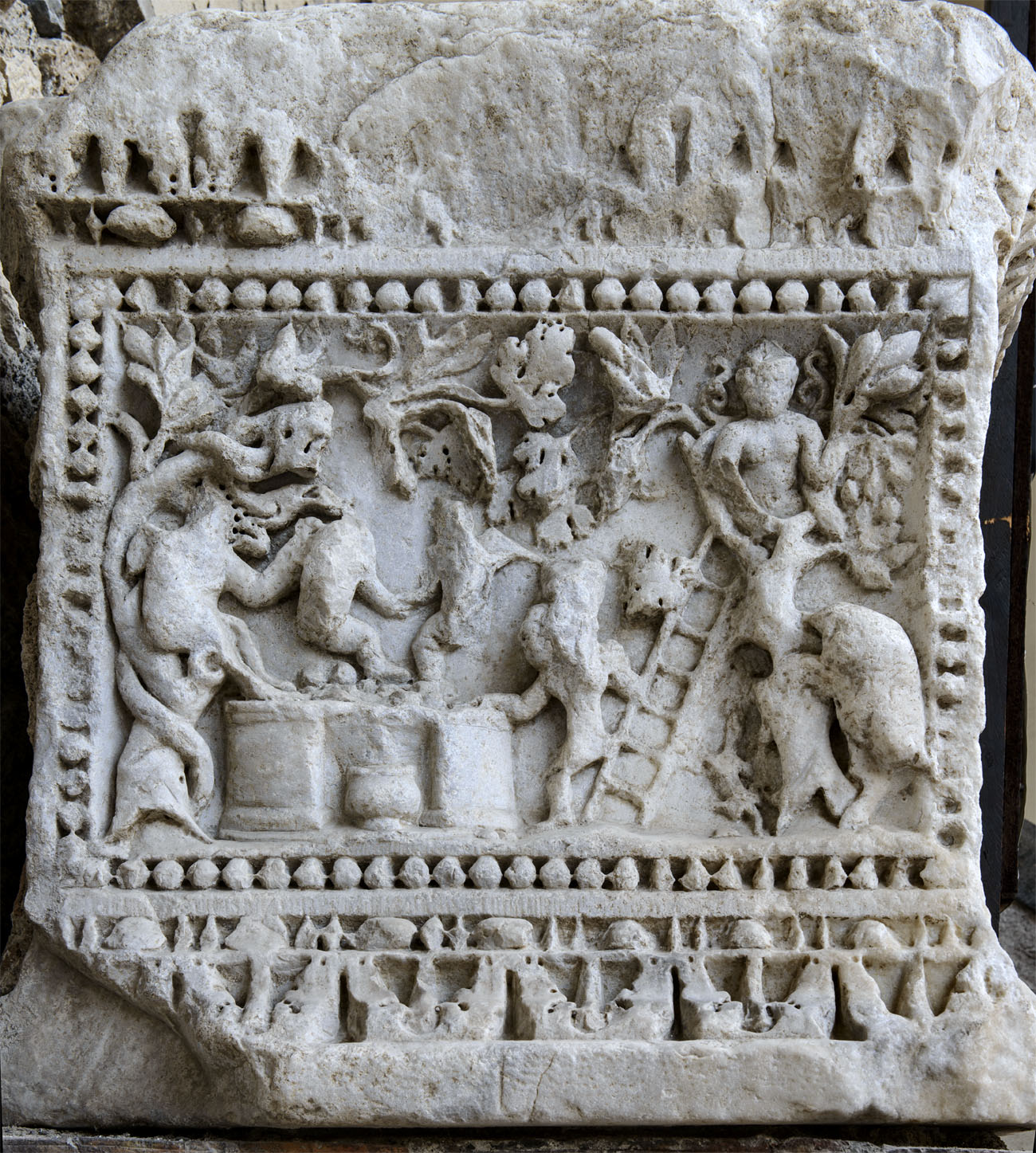 Base of a column with dionysiac scenes (left side). Vintage scene (vindemialia). Marble. Severan age. Salerno, Cathedral