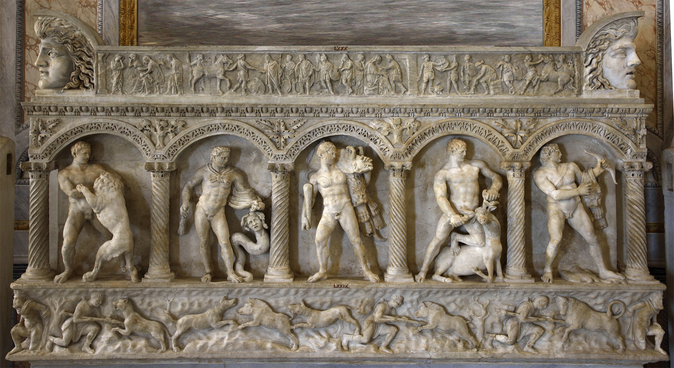 Front of columnar sarcophagus showing the Labours of Heracles and scenes of hunt. Frieze of a sarcophagus lid showing Amazons at the Trojan War. Acroteria. Front wall: asiatic marble. 160 CE.  Inv. No. LXXIX / 79. Lid: Italian marble. 2nd cent. CE.  Inv. No. LXXX / 80. Acroteria: asiatic marble. Rome, Museum and Gallery of Villa Borghese, Room II