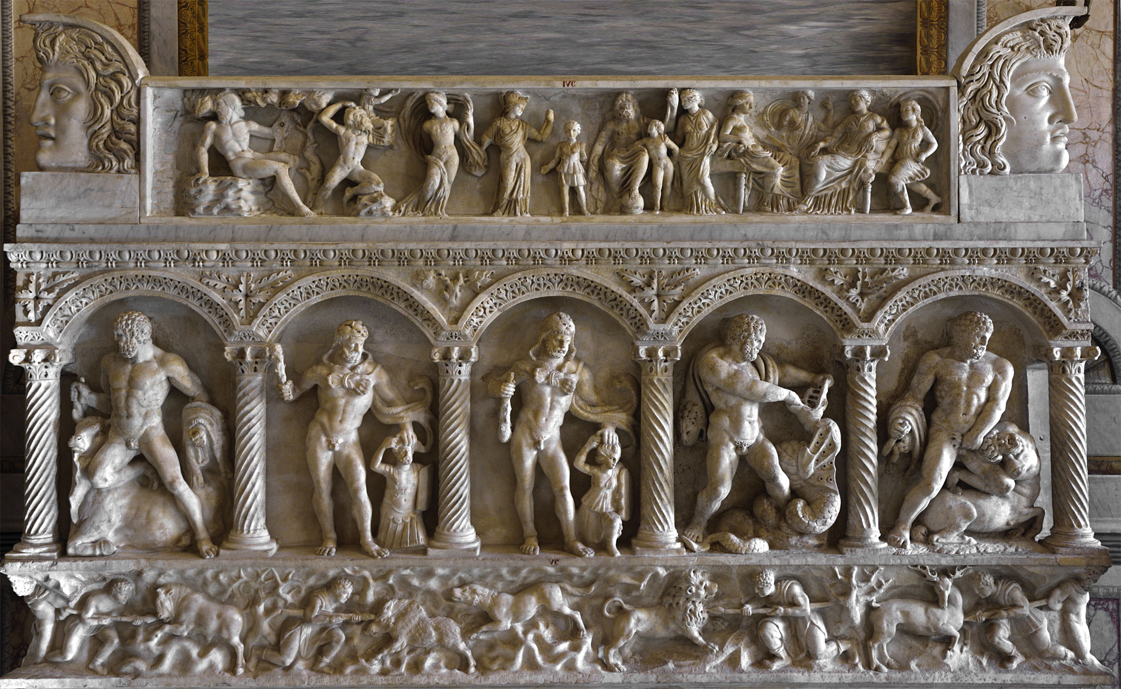 Rear of columnar sarcophagus showing the Labours of Heracles and scenes of hunt. Frieze of a sarcophagus lid showing the presentation of Apollo and Artemis to Zeus. Acroteria. Rear wall: asiatic marble. 160 CE.  Inv. No. VC. Lid: Italian marble. Ca. 150 CE.  Inv. No. IVC. Rome, Museum and Gallery of Villa Borghese, Room II