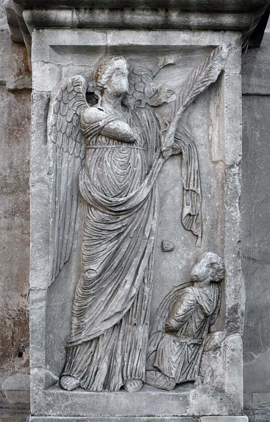 Winged Victory and a captured barbar. Relief of the column plinth. Marble. 312—315 CE. Rome, Arch of Constantine, North face