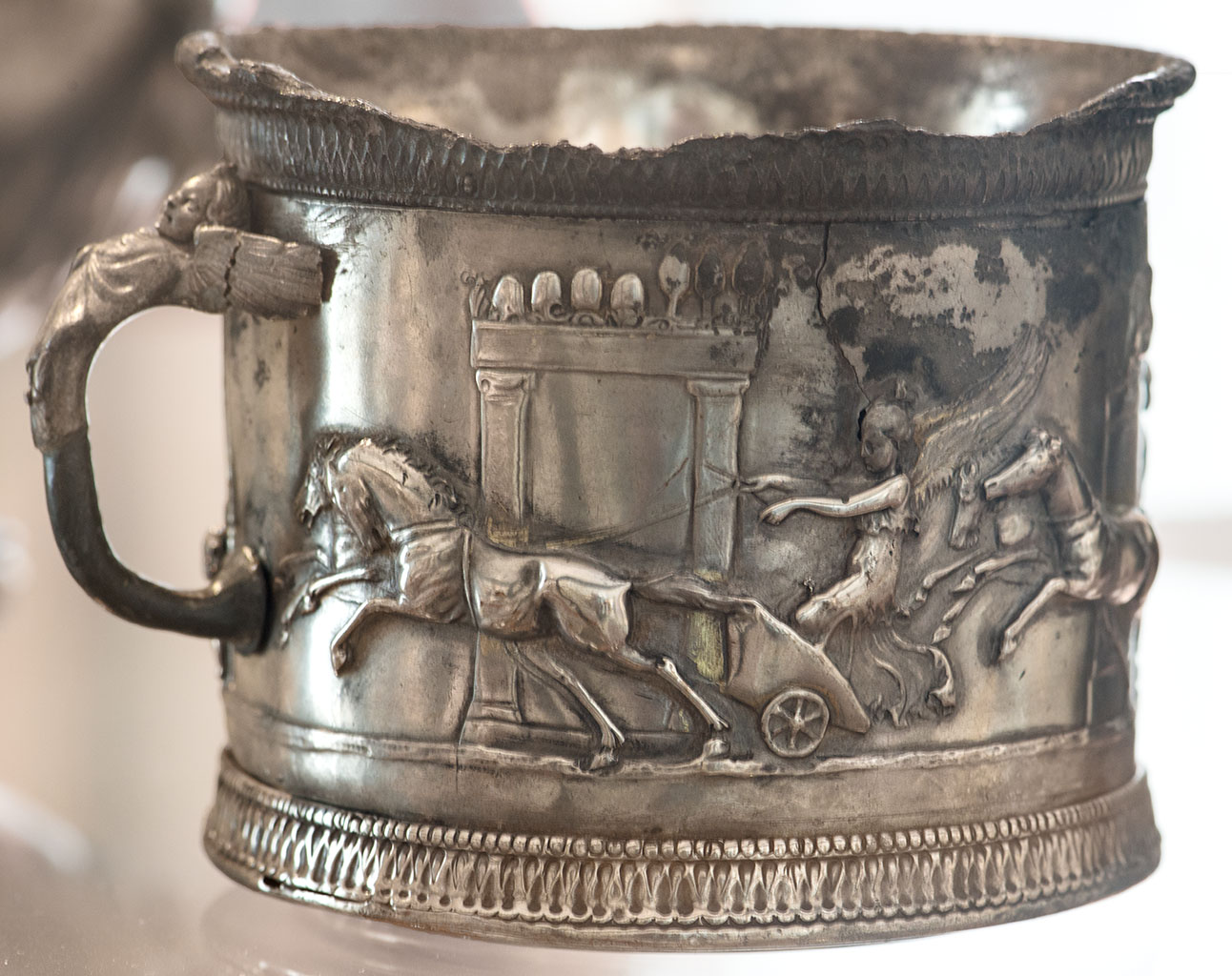 A single-handed cup with with a chariot race of amors in the Circus Maximus. Silver with traces of gilding. 1st century BCE—1st century CE. H. 8 cm, d. 9.5 cm, weight 355 g. Inv. No. 145510. Naples, National Archaeological Museum