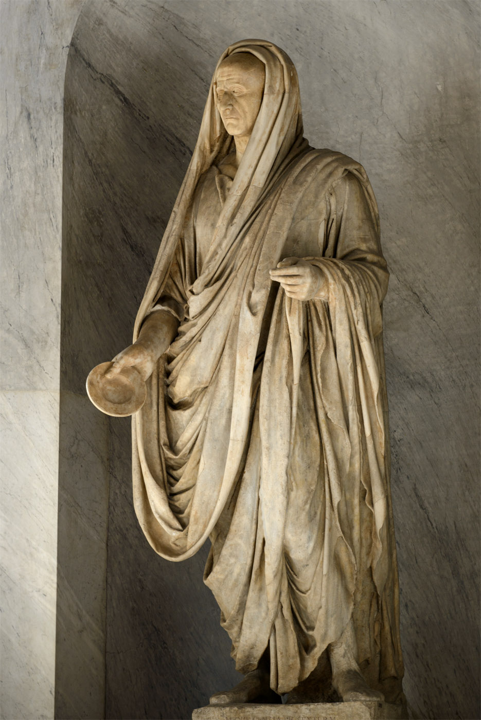 A portrait of a Roman in toga (with a head from a different statue). Marble. 130—140 CE. Head: 30—20 BCE. Inv. No. 2355. Rome, Vatican Museums, Pius-Clementine Museum, Room of the Biga, 11
