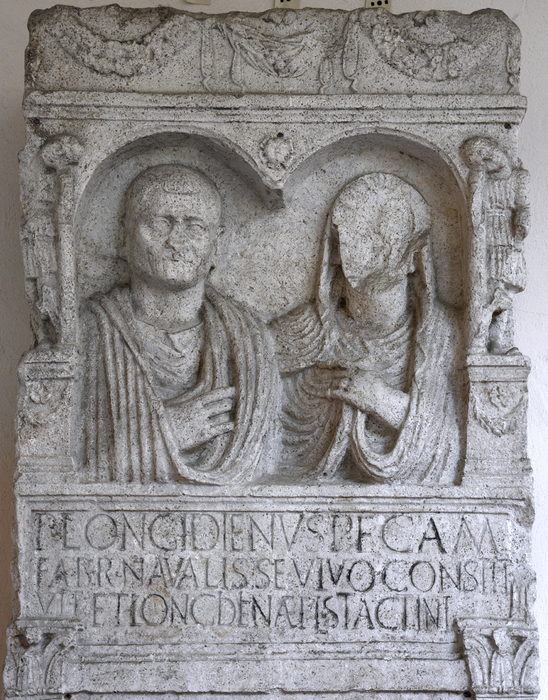 "Funerary stele containing a portrait busts and a scene of shipbuilding (""the Longidien stele""). The upper register. Limestone. First half of the 1st century CE (the museum dating). Inv. No. 7. Ravenna, National Museum, First cloister"
